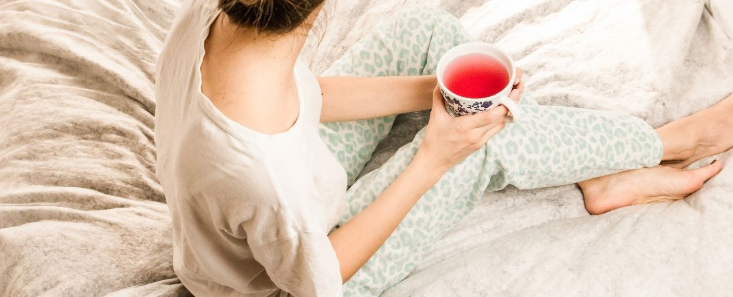 Girl sitting on a bed with a cup of tea in hand.