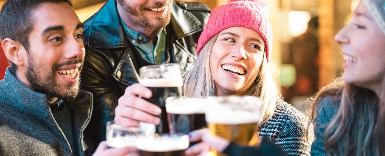 People toasting beer glasses in winter apparel.