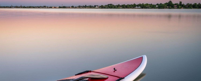 Paddleboard on a lake at sunset.