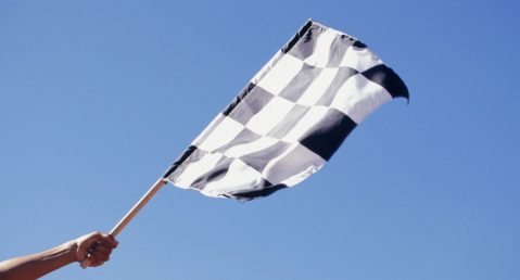 Person holding checkered flag with a blue sky background.