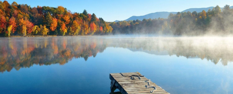 Dock on a lake with fall foliage around.