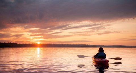 Person kayaking on a lake at sunset.